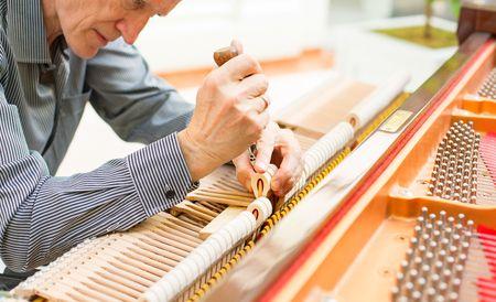 man repairing a grand piano
