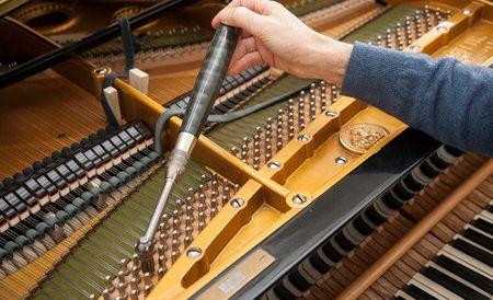 man tuning a grand piano